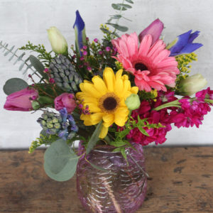 a brightly colored arrangement with yellow, pink, and blue flowers